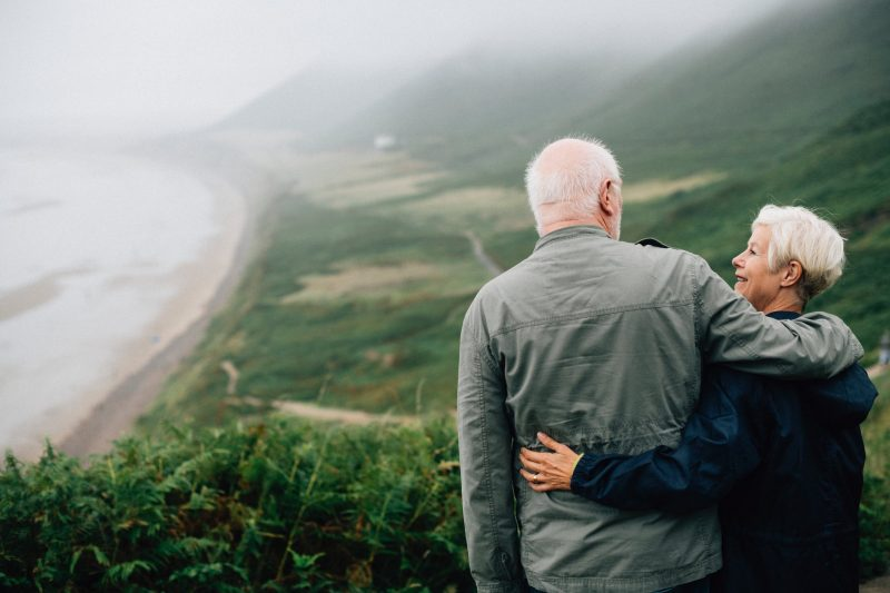 Two retirees standing together looking at the ocean and green grass