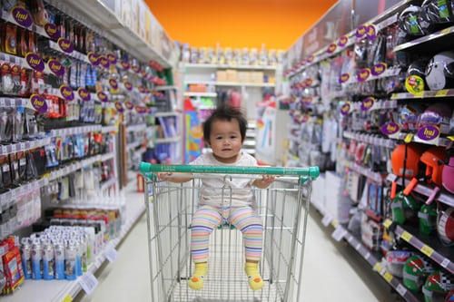 A baby in a shopping card in an aisle