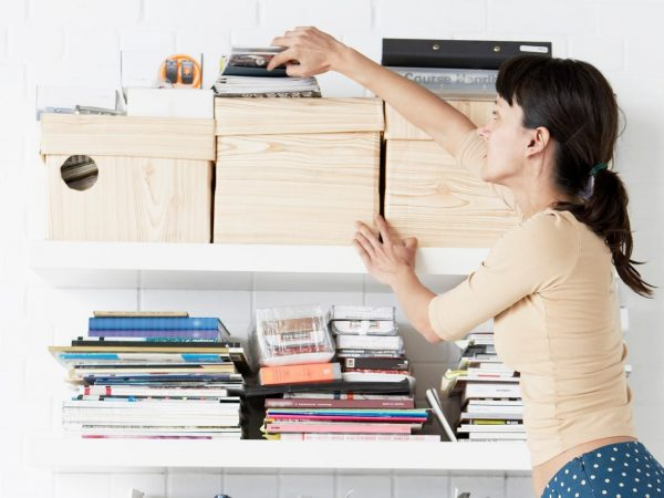 a woman decluttering her office space while getting something from the shelf