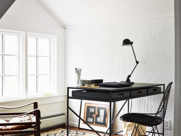 a simple home office with a lamp on the desk