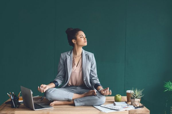 a woman working from home while meditating on top of her desk