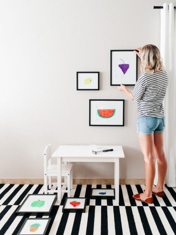 a woman hanging picture frames on her wall