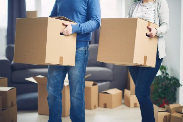 a young couple lifting boxes and moving it out of their house