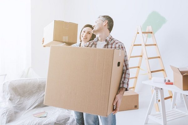 a couple carrying boxes out of their home during a home renovation