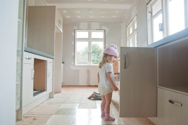 a small girl opening the cabinet door