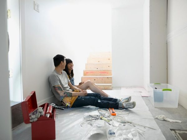 a young asian couple sitting on the floor of their unfinished house