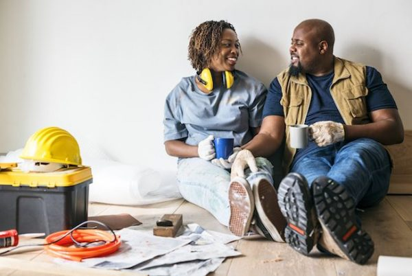 a black couple sitting on the floor of their living room that's being renovated