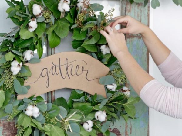 A woman decorating her door with a garland