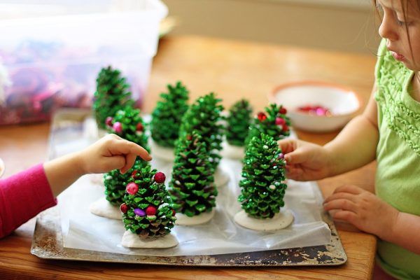 Two girls decorating pinecones on a table