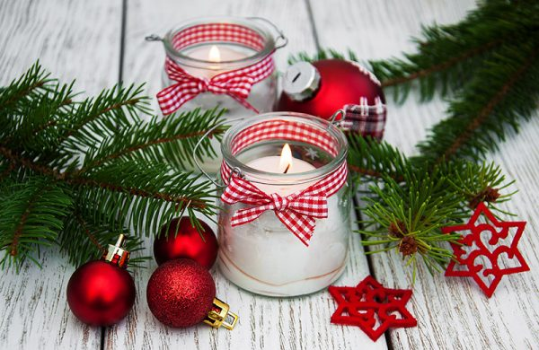 Two lit candles in a glass containers surrounded by Christmas nicknacks