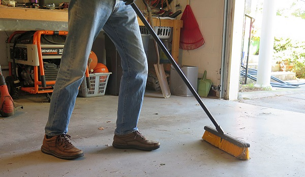 A man sweeping the garage floor with a broom